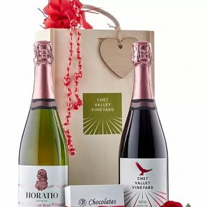 A picture of Chet Valley Vineyard Red Kite sparkling wine and Horatio pink wine next to a large decorative wooden box and a small box of salted caramel chocolates.