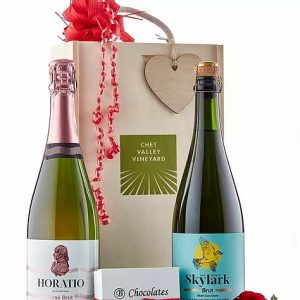 A picture of Chet Valley Vineyard Skylark sparkling wine and Horatio pink wine next to a large decorative wooden box and a small box of salted caramel chocolates.