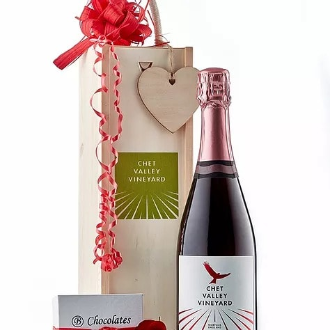 A picture of Chet Valley Vineyard Pink Horatio sparkling wine next to a decorative wooden box and a small box of salted caramel chocolates.