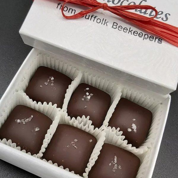An open box of six salted caramel chocolates.