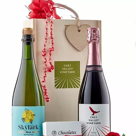 A picture of Chet Valley Vineyard Skylark sparkling wine and Red Kite wine next to a large decorative wooden box and a small box of salted caramel chocolates.
