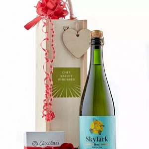A picture of Chet Valley Vineyard Skylark sparkling wine next to a decorative wooden box and a small box of salted caramel chocolates.