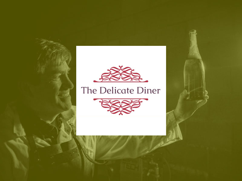 The Delicate Diner logo placed over an image of the Chet Valley Vineyard owner holding up a bottle of wine.