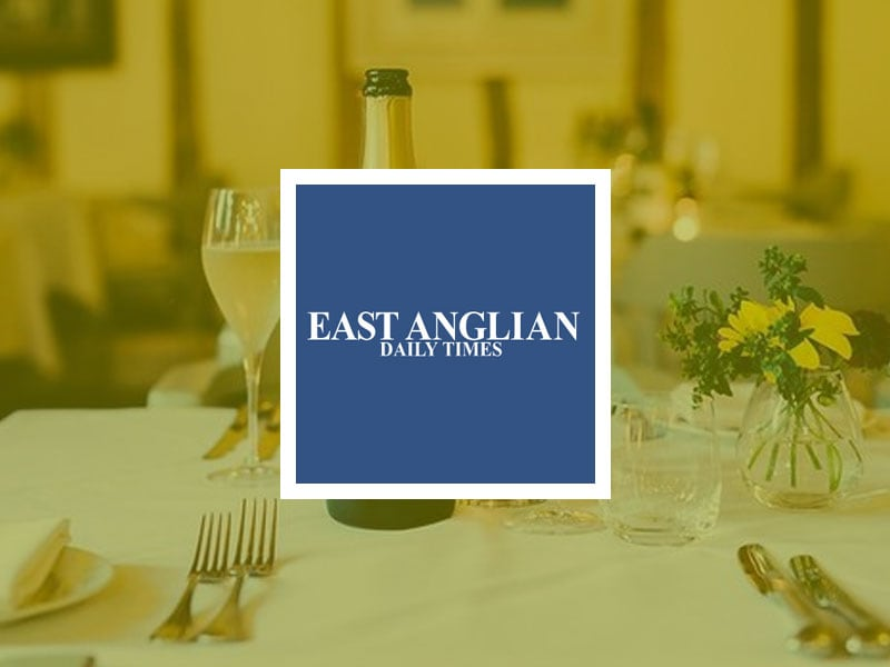 East Anglian Daily Times logo placed over an image of set table with an open bottle of wine.