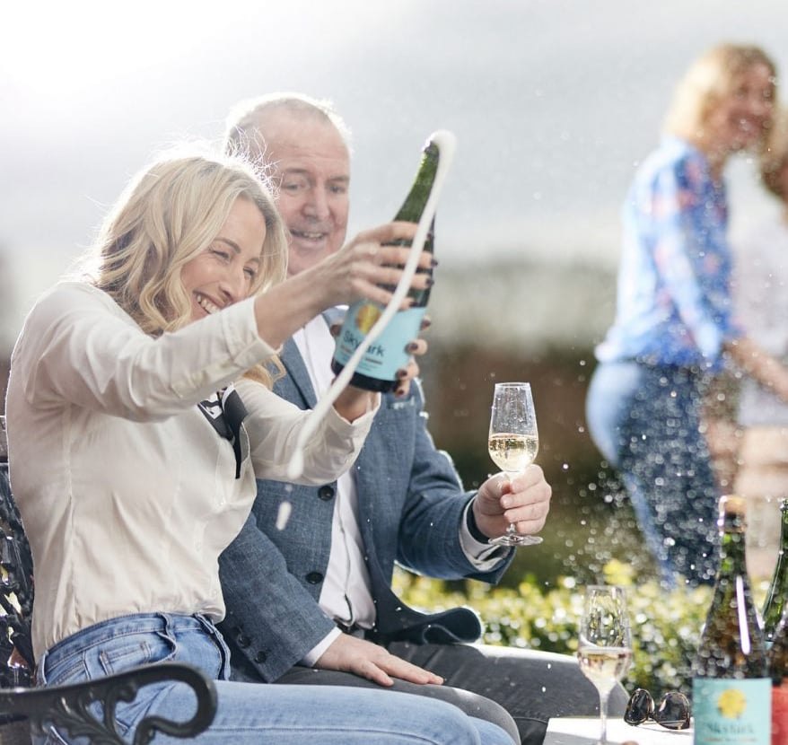 An image of a woman popping open a bottle of Chet Valley Vineyard sparkling wine.