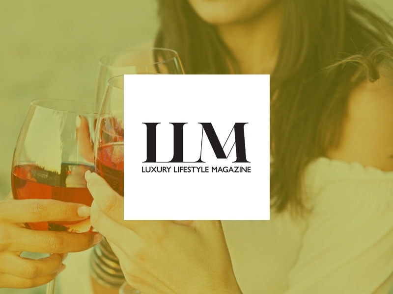 The Luxury Lifestyle Magazine logo placed over an image of a woman holding a glass of wine, clinking with two other glasses.