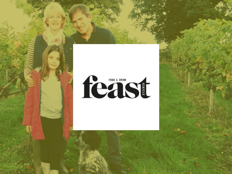 A Feast Norfolk logo placed over an image of the Chet Valley Vineyard owners standing next to vines with a young girl and a dog.