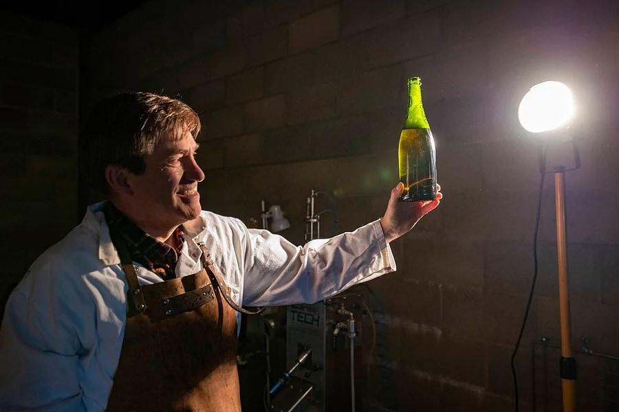 The Chet Valley Vineyard winemaker, John Hemmant, standing indoors, holding up a green bottle towards a lamp.