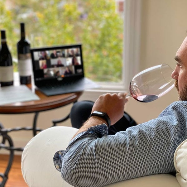 A man drinking red wine while on a video call on a laptop placed in front of him, with more bottles of wine behind the laptop.